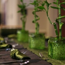 Chocolate pintuck linen with a moss colored crush runner, moss crush napkins, aster flatware, and kiwi square vases with lucky bamboo.