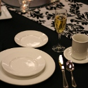 elegant black table with white plates and decorative runner.