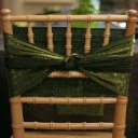 Natural wood chiavari chair wrapped with a moss crush sash.