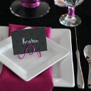 A simple black place card written in silver letters with a pink wire stand.