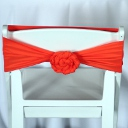 A white garden chair with an orange rosette sash