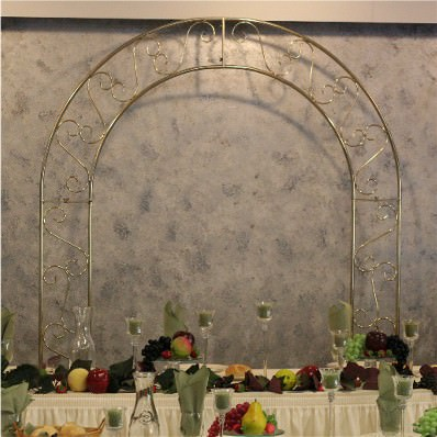 A tall brass arch is placed behind an ivory bridal table. The table is decorated with tall candle-filled centerpieces and sage green accents.