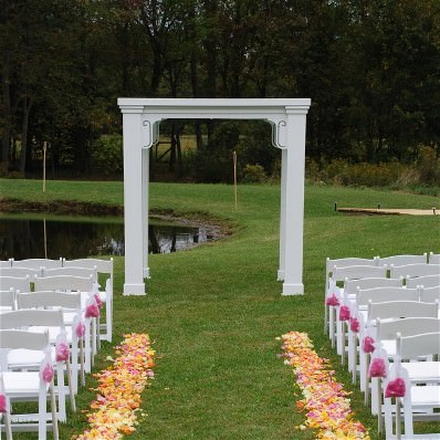 A 7' square arch appears at the end of an aisle lined with orange and pink rose petals. On either side of the aisle, rows of white garden chairs with pink bows are visible.