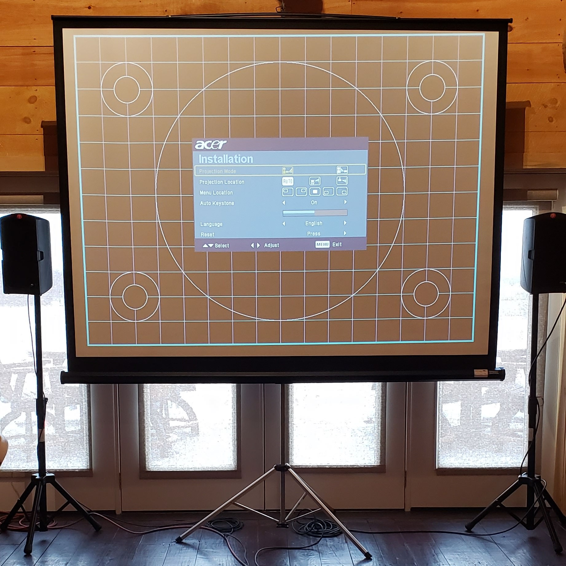 The bottom portion of a projection screen is visible, along with it's tripod in front of a burgundy background..